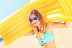 Beautiful woman with mattress on the beach Royalty Free Stock Image