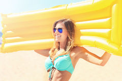 Beautiful woman with mattress on the beach Stock Photography