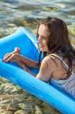 Beautiful  woman on a mattress on the sea Stock Image