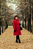 Beautiful woman. The  mature beautiful woman in red topcoat,  outdoor in park, autumnal day Stock Photo