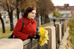 Beautiful woman. The  mature beautiful woman in red topcoat,  outdoor in park, autumnal day Stock Images
