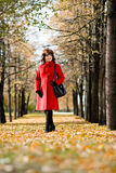 Beautiful woman. The  mature beautiful woman in red topcoat,  outdoor in park, autumnal day Royalty Free Stock Photo