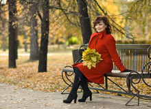 Beautiful woman. The  mature beautiful woman in red topcoat,  outdoor in park, autumnal day Royalty Free Stock Image