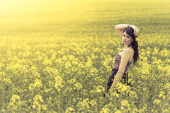 Beautiful woman in meadow of yellow flowers with arm up. Attractive genuine young girl enjoying the warm summer sun in a wide green and yellow meadow. Part of Royalty Free Stock Photography