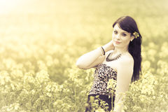 Beautiful woman in meadow of yellow flowers and bright environme Stock Image
