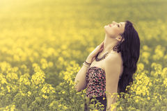 Beautiful woman in meadow of yellow flowers with face up. Attractive genuine young girl enjoying the warm summer sun in a wide green and yellow meadow. Part of Stock Images