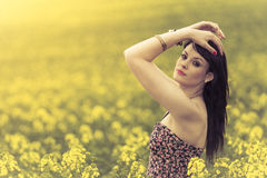Beautiful woman in meadow of yellow flowers with hands up. Attractive genuine young girl enjoying the warm summer sun in a wide green and yellow meadow. Part of Stock Photos