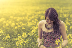 Beautiful woman in meadow of yellow flowers looking down. Attractive genuine young girl enjoying the warm summer sun in a wide green and yellow meadow. Part of Stock Photography