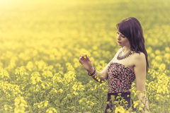 Beautiful woman in meadow of yellow flowers looking at flower. Attractive genuine young girl enjoying the warm summer sun in a wide green and yellow meadow. Part Stock Photography