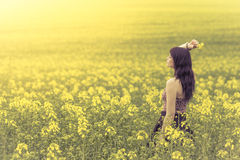 Beautiful woman in meadow of yellow flowers from side behind. Attractive genuine young girl enjoying the warm summer sun in a wide green and yellow meadow. Part Royalty Free Stock Photography