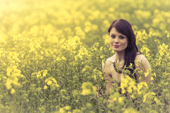 Beautiful woman in meadow of yellow flowers sitting down. Attractive genuine young girl enjoying the warm summer sun in a wide green and yellow meadow. Part of Royalty Free Stock Photo