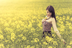 Beautiful woman in meadow of yellow flowers touching flower. Attractive genuine young girl enjoying the warm summer sun in a wide green and yellow meadow. Part Royalty Free Stock Photo