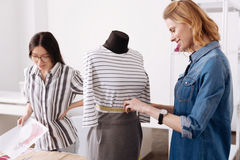 Beautiful woman measuring waist of a dress. Perfect size. Charming young tailor measuring waist of a dress hanging on a mannequin and looking pleased with the Stock Photos