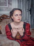 Beautiful woman in medieval dress on the armchair Royalty Free Stock Photography