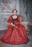 Beautiful woman in medieval dress on the armchair Stock Image