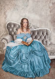 Beautiful woman in medieval dress with book on the sofa Royalty Free Stock Images