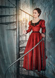 Beautiful woman in medieval dress with candelabrum. On the stairway Royalty Free Stock Photo