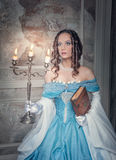 Beautiful woman in medieval dress with candelabrum. Beautiful young  woman in long blue medieval dress with candelabrum and book Royalty Free Stock Photo