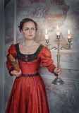 Beautiful woman in medieval dress with candelabrum. Beautiful young  woman in long red medieval dress with candelabrum and book Royalty Free Stock Photography