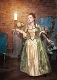 Beautiful woman in medieval dress with candle Stock Image
