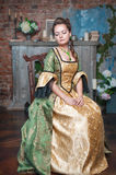 Beautiful woman in medieval dress on the chair Stock Image