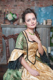 Beautiful woman in medieval dress on the chair Royalty Free Stock Photography