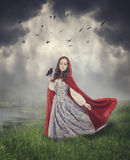 Beautiful woman in medieval dress and cloak with crow. Outdoor Royalty Free Stock Photo