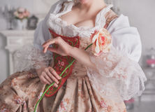 Beautiful woman in medieval dress holding rose. Beautiful woman in medieval dress holding pink rose Stock Photo