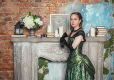Beautiful woman in medieval dress near fireplace Stock Images