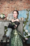 Beautiful woman in medieval dress near fireplace Royalty Free Stock Image