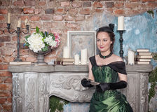 Beautiful woman in medieval dress near fireplace Royalty Free Stock Images