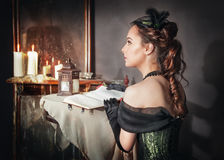 Beautiful woman in medieval dress near mirror Royalty Free Stock Photography