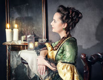 Beautiful woman in medieval dress near mirror Stock Photo