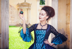 Beautiful woman in medieval dress with perfume bottle Stock Photos