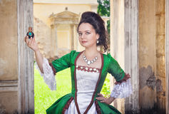 Beautiful woman in medieval dress with perfume bottle Stock Photo