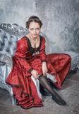 Beautiful woman in medieval dress putting stockings Royalty Free Stock Image