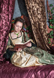 Beautiful woman in medieval dress reading book royalty free stock photos