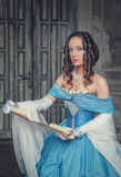 Beautiful woman in medieval dress with scroll letter. Beautiful young woman in blue medieval dress with scroll letter in the room Royalty Free Stock Photography