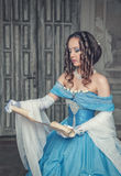Beautiful woman in medieval dress with scroll letter. Beautiful young woman in blue medieval dress with scroll letter in the room Royalty Free Stock Image