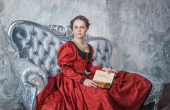 Beautiful woman in medieval dress on the sofa with book Royalty Free Stock Photography