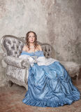 Beautiful woman in medieval dress on the sofa Stock Images