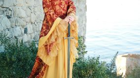 Beautiful woman in medieval dress with sword. Young woman in medieval dress with sword near the water fortress stock video