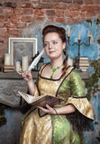 Beautiful woman in medieval dress writing in diary Royalty Free Stock Image