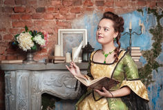 Beautiful woman in medieval dress writing in diary Stock Image