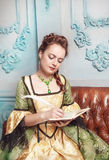 Beautiful woman in medieval dress writing in diary Stock Photo