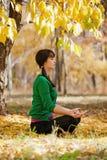 Beautiful woman meditates in autumn park Stock Photos