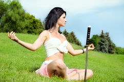 Beautiful woman meditates on green lawn Stock Photo