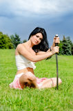 Beautiful woman meditates on green lawn summer. Beautiful woman meditates on green lawn with katana sword stuck into the ground Stock Photography