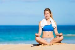 Beautiful woman meditating on the beach Stock Photos
