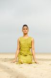 Beautiful woman meditating at the beach Royalty Free Stock Images
